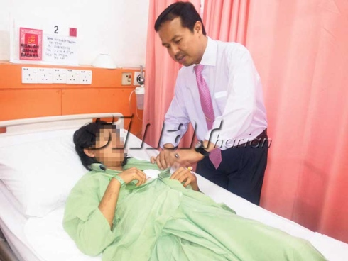 Dr Imi Sairi (kanan) merawat seorang pesakit payudara di HRPZII, hari ini.